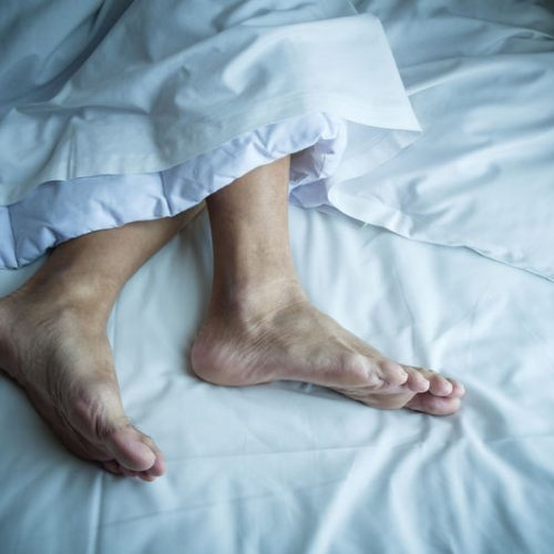Exposed feet of an adult man sleeping in bed